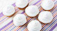 White cupcakes on the striped linen napkin top view