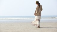 Stylish mature woman walking on the beach