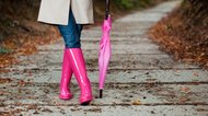 Woman walking down a sidewalk with a pink umbrella and boots