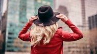 Stylish woman wearing hat walking on city streets