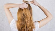 Red-haired young woman combing hair with wooden comb