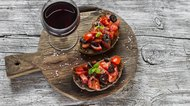 Tomatoes and olives bruschetta and a glass of red wine
