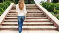 Rear view of young woman going up stairs in park