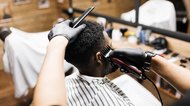 African American man having wave cut at barber shop