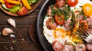 Closeup fried eggs with sausage and tomatoes in frying pan.