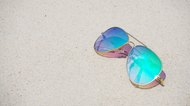 Fashionable mirror sunglasses on sand beach background