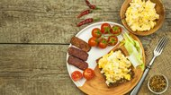 Scrambled eggs with bread and salami. Egg breakfast