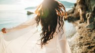 wind in hair dreamy girl with sunflare on beach