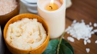 close up of natural sugar scrub and candle on wood