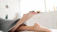 Lying on bed female legs under blanket