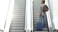 Traveling man going up escalator with suitcase and bag
