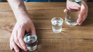 Shot glasses of vodka on table