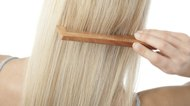 Blonde woman brushing her straight hair