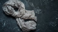 Grey silk scarf on dark black vintage background