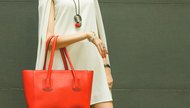 Fashionable beautiful red handbag on the arm of the girl