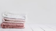 Stack of clean washcloths on wooden table in bathroom.