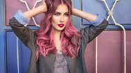 fashion model with curly pink hair posing near colorful wall