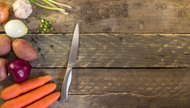Onion , garlic , potato , carrot , and knife on a wooden table. Healthy food. Organic vegetables on wood
