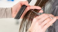 Hairdresser cutting long hair