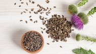 Seeds of a milk thistle with flowers on wooden table