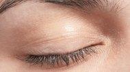 Close-up of woman's eyelid including eyelashes and eyebrow