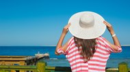woman in a big hat looking at the sea