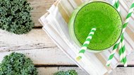 Green kale smoothie with straws overhead view