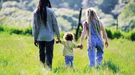 Family walking in grass field
