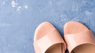 Pair of woman pink patent sandals on blue background