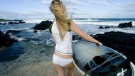 USA, Hawaii, Rear view of young woman carrying surfboard on the beach