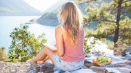 Blond teenager girl sitting on a cover, picnic, mountains