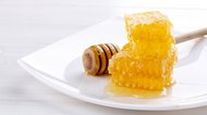 Stack of honeycombs with honey on white