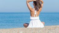 Girl in white sits on pebble seashore correcting hairstyle