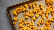 Diced butternut squash cubes on parchment paper lined baking tray