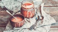Salted caramel sauce in a rustic glass jar and brown