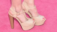 High heeled shoes with wooden heel on pink carpet
