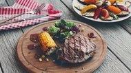 Grilled beef steak closeup on dark wooden table background