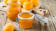 Homemade organic apricot jam in glass jar and ripe apricots