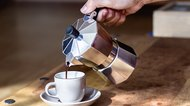 Woman's hand holding coffee maker while pouring coffee on cup