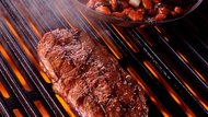 Rib eye steak on grill with beans