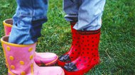 Close-up of the feet of two young girls wearing wellingtons