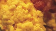 close-up of scrambled eggs served with bacon (blurred)