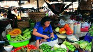 Woman selling vegetables at Asian market