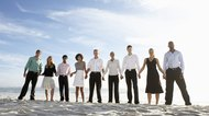 Nine businessmen and women holding hands on beach, portrait
