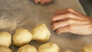 Close-up of hands of baker making buns
