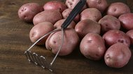 old potato masher with red potatoes