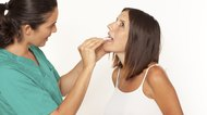 Female doctor checking for sore throat