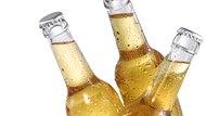 Three dewy beer bottles on ice