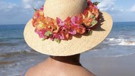 Woman wearing a straw hat on the beach, rear view