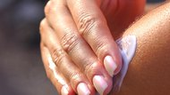 A close-up of a woman's hand applying lotion
